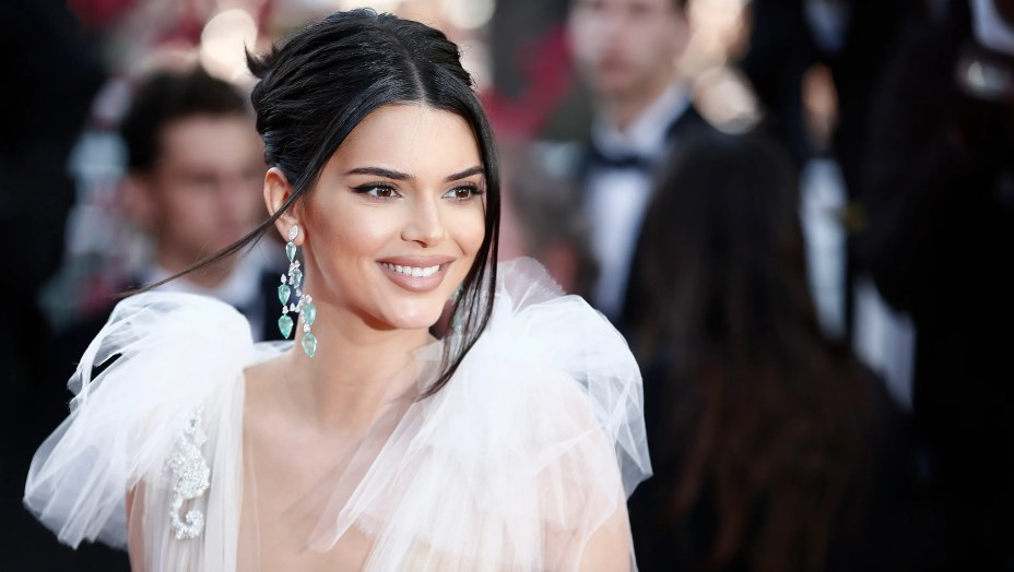 Kendall Jenner wearing a white dress and dangling green earrings