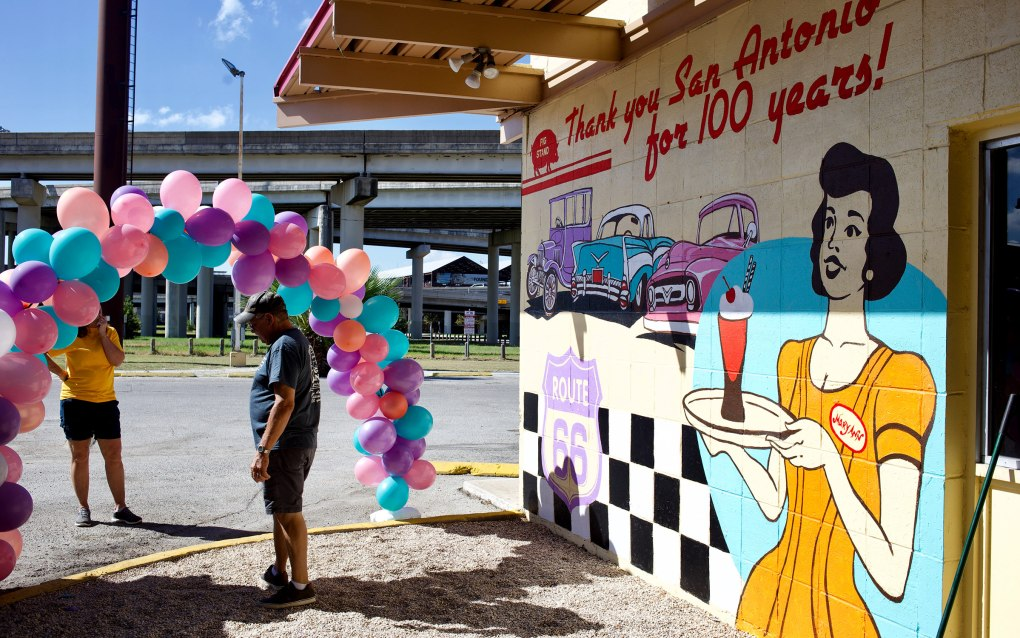 Volunteers set up a balloon arch outside a mural on the side of the Pig Stand.