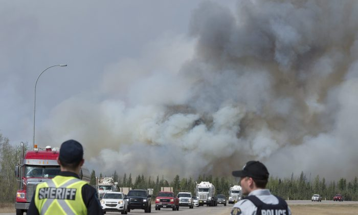Police watch a convoy of cars and trucks pass a wildfire as they are evacuated from Fort McMurray, Alberta, on  May 7, 2016. Federal scientists are predicting the 2020 summer wildfire season could be well above average for much of Canada, especially Western provinces.   (Jonathan Hayward /The Canadian Press via AP)