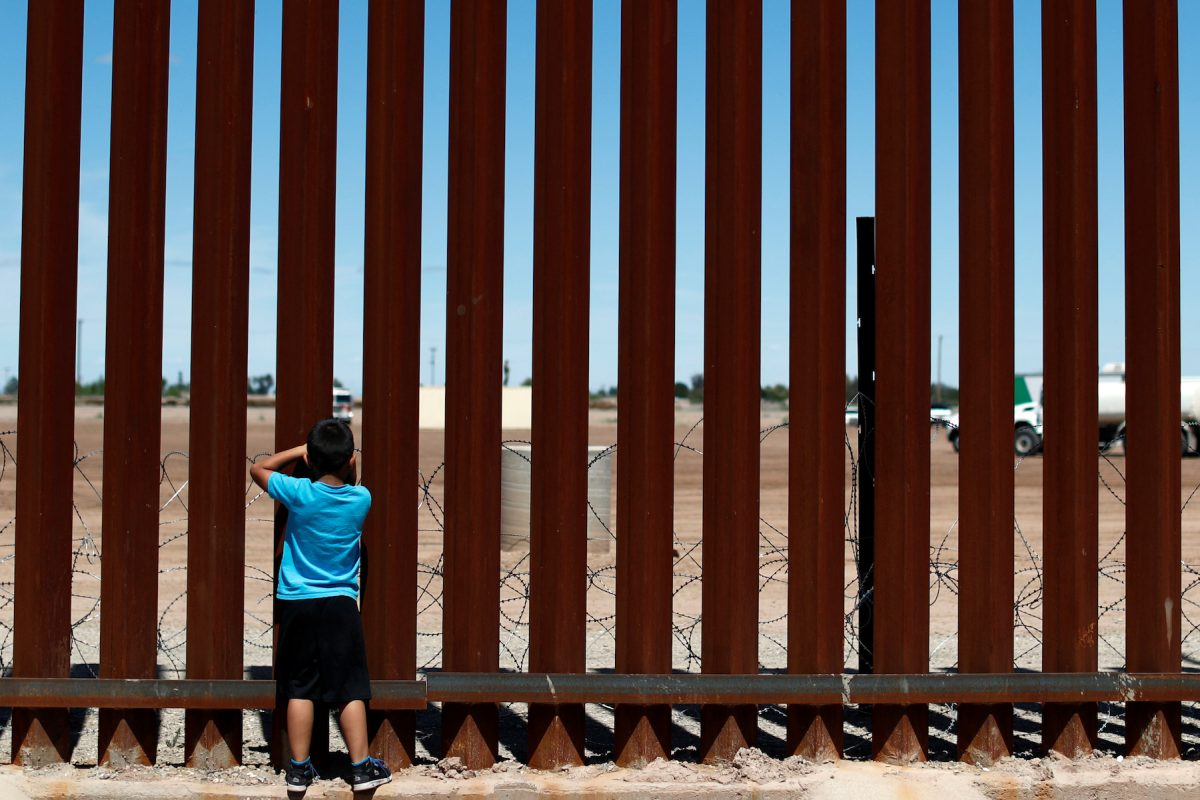 A child looks through the border wall during the visit of U.S. President Donald Trump to Calexico, California, as seen in Mexicali