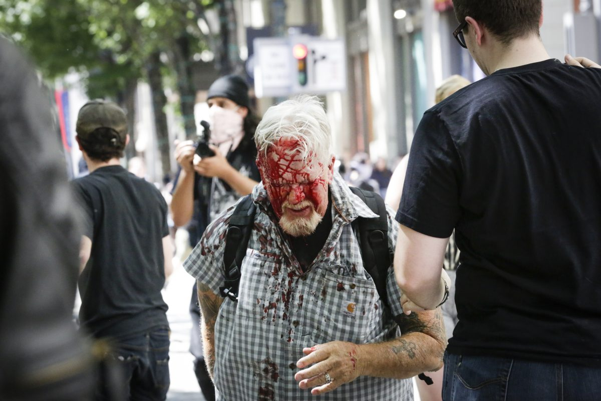 a man covered with his face in blood walks in portland