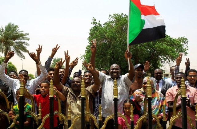 Sudanese people carry their national flag
