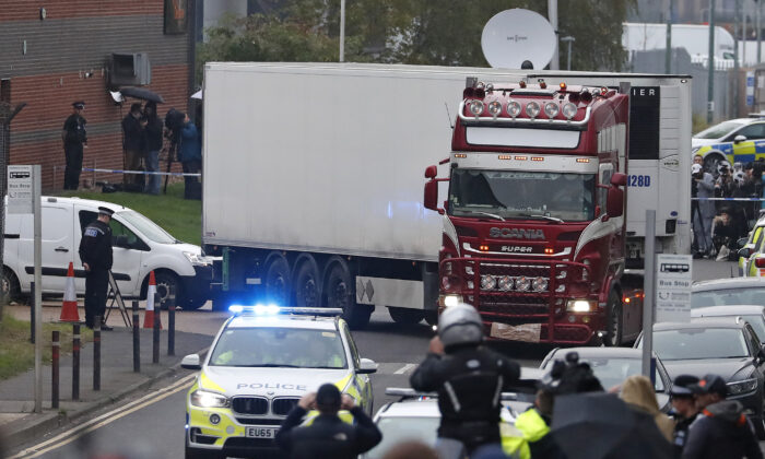 Police escort the truck, that was found to contain a large number of dead bodies, as they move it from an industrial estate in Thurrock, south England, on Oct. 23, 2019. (Alastair Grant/AP)