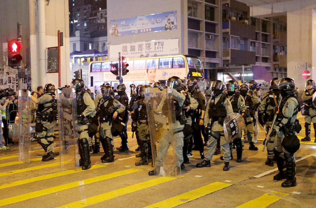 Riot police officers block the street