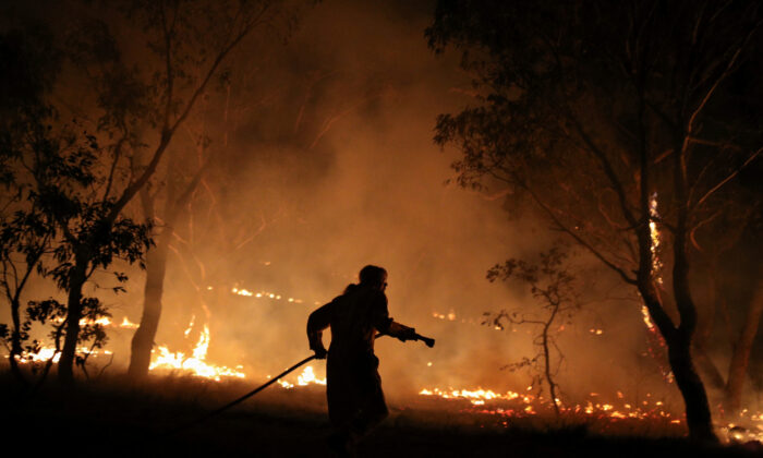A firefighter from a local brigade works to extinguish flames after a bushfire burnt through the area in Bredbo, New South Wales, Australia, on Feb. 2, 2020.  (Loren Elliott/Reuters)