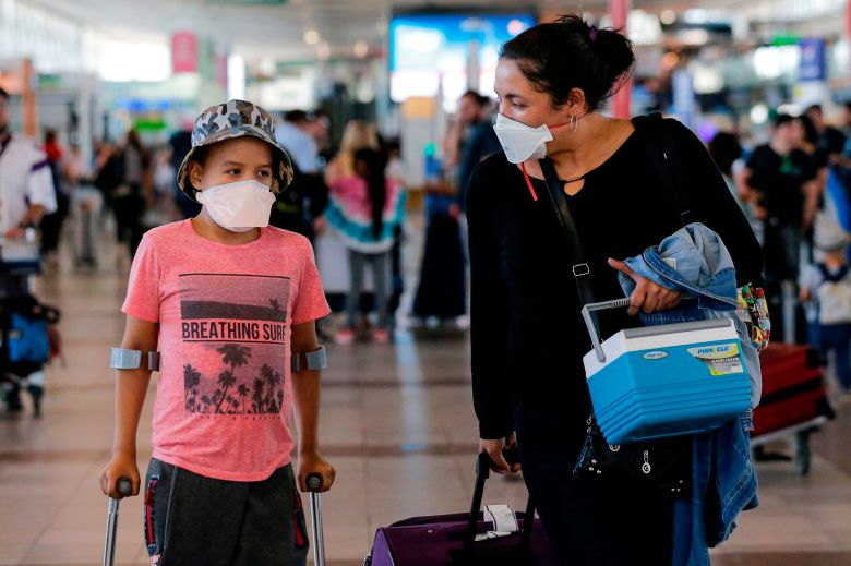 Passengers walk with protective masks