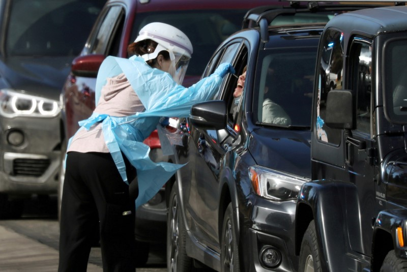 Health care worker tests people at a drive-thru