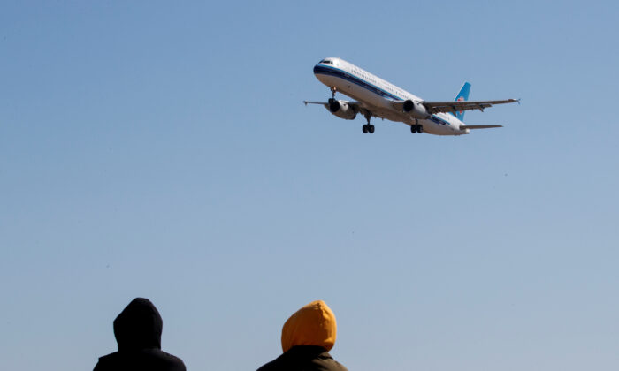 People watch a plane of China Southern Airlines land at Beijing Capital International in Beijing as the country is hit by an outbreak of the CCP Virus, China, March 13, 2020. (Reuters/Thomas Peter)