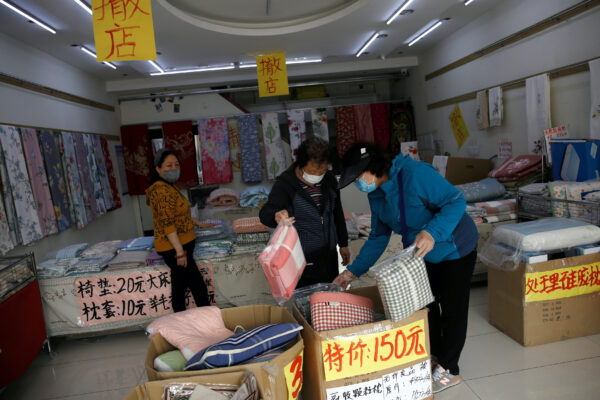 Customers wearing face masks shop bed linen under business closure notices inside a home linen store whose business has been struggling since the coronavirus disease (COVID-19) outbreak, in Beijing