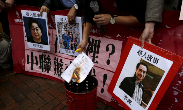 A pro-democracy demonstrator burns a letter next to pictures of missing staff members of a publishing house and a bookstore, including Gui Minhai, a China-born Swedish national who is the owner of Mighty Current,  Cheung Jiping, the business manager of the publishing house and Causeway Bay Books shareholder Lee Bo (L-R), during a protest to call for an investigation behind their disappearance, outside the Chinese liaison office in Hong Kong, China, on Jan. 3, 2016. (Tyrone Siu/Reuters)