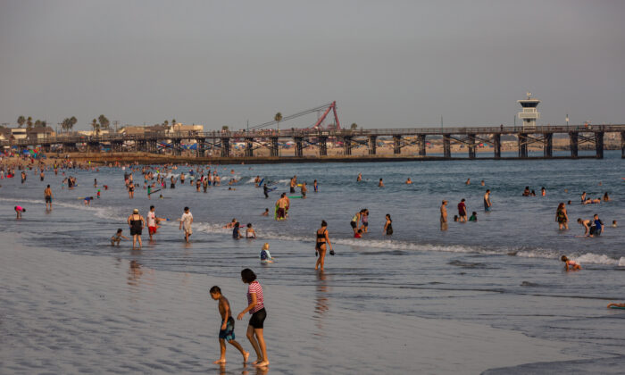 Beachgoers cool off in the ocean at Seal Beach, Calif., during a heat wave on Sept. 6, 2020. (John Fredricks/The Epoch Times)