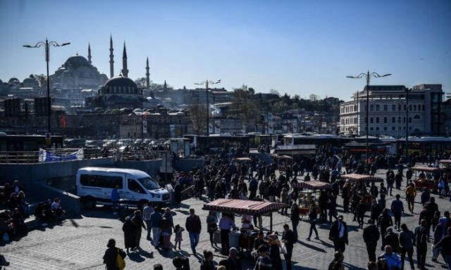 People walk in the district of Eminonu, next to bread and fish street vendors, as the Suleymaniye Mosque is seen in the background during a sunny day in Istanbul, Turkey, on April 3, 2018. (Ozan Kose/AFP via Getty Images)