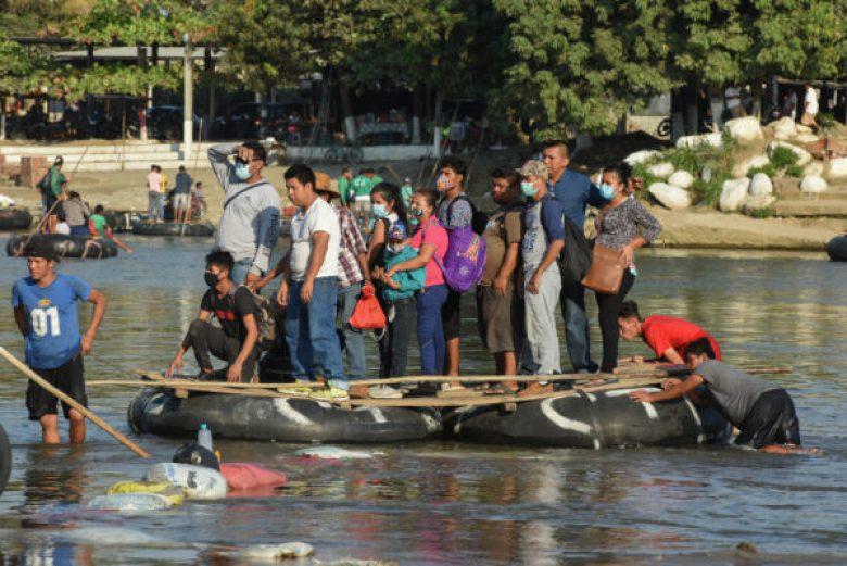 People cross the Suchiate River on a raft