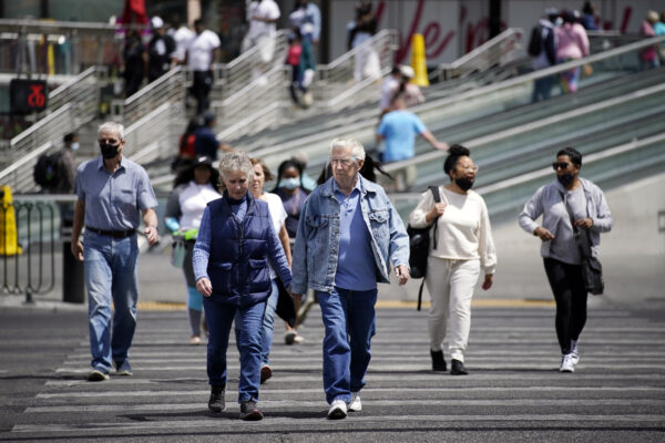 Masked and unmasked pedestrians walk across Las Vegas Boulevar