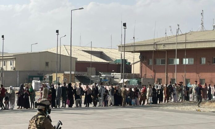 Afghan evacuees line up before boarding one of the last Italy's military aircraft C130J during evacuation at Kabul's airport, Afghanistan, on Aug. 27, 2021. (Italian Ministry of Defence/Handout via Reuters)