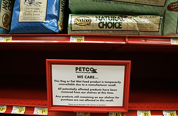 A sign explains why a store shelf is empty of pet food after it was pulled from the shelves at Petco