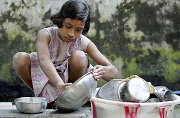 An 11-year-old child laborer washes dishes at a house in Siliguri, India. Photo courtesy of Rupak De Chowdhuri / Reuters