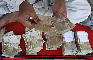 A Pakistani money changer counts Pak rupees in Karachi, Pakistan on Friday, Oct. 24, 2008. Pakistan.