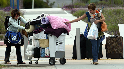 Bria Reiniger, left, and Taylor Zompolis help each other move in to a dormitory at California State University Monterey Bay in Marina, Calif.