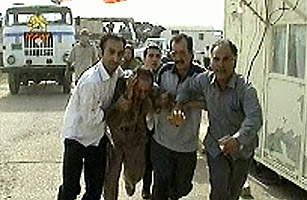 An injured man being assisted at Camp Ashraf in Iraq
