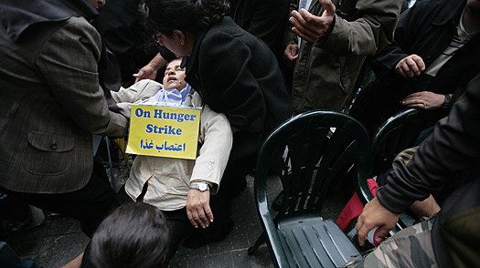 Iranian protester Farzaneh Dadkhah is helped after collapsing on the sixth day of a hunger strike outside the US embassy in central London, on August 4, 2009.