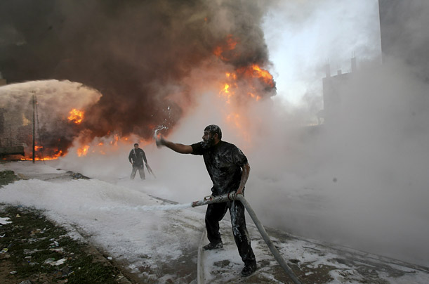 A medicine storehouse is the collateral damage caused by Israeli missiles as a nearby fuel tank is engulfed in flames