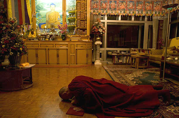 His holiness the Dalai Lama prostrates himself before a statue of Buddha at his residence in Dharamsala, India.