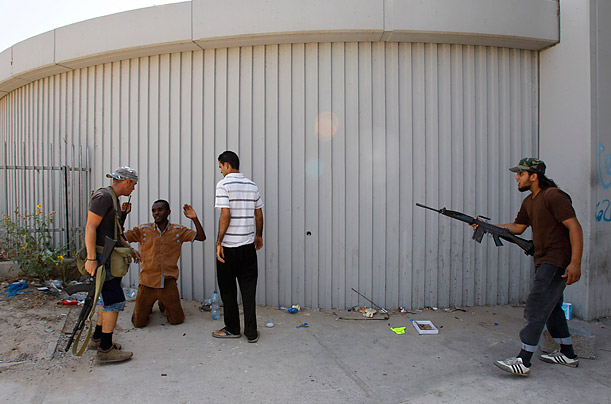 A man, second from left, accused of being a loyalist mercenary of Libyan leader Muammar Gaddafi kneels on the ground after being arrested in Tripoli on August 28, 2011,  at one of several checkpoints in the city.