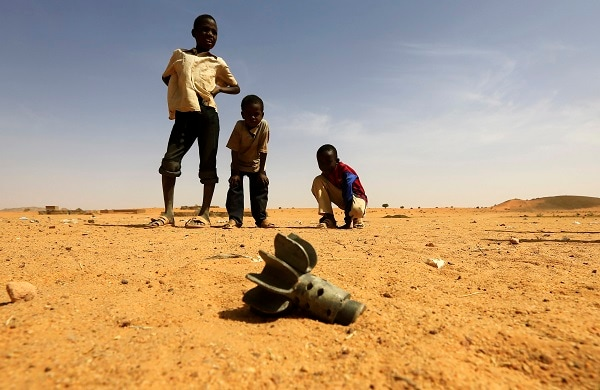 Children look at the fin of a mortar projectile that was found at the Al-Abassi camp for internally displaced persons, after an attack by rebels, in Mellit town, North Darfur in this March 25, 2014 (REUTERS/Mohamed Nureldin Abdallah)