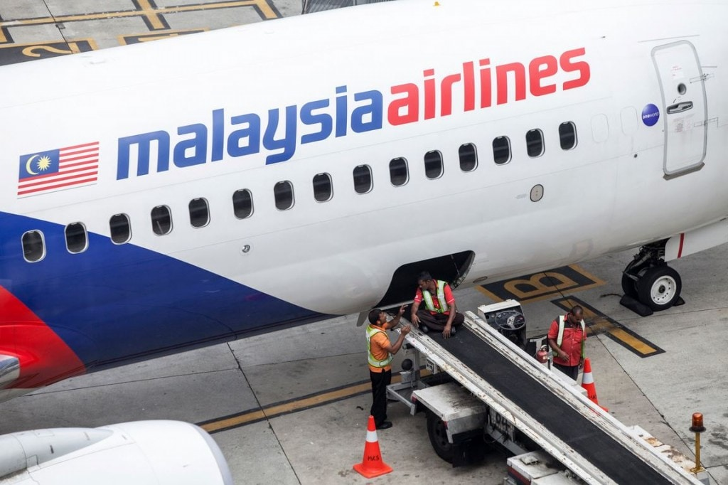 Ground staff take a break while loading an aircraft operated by Malaysian Airlines System Bhd. (MAS) at Kuala Lumpur International Airport in this 2014 file photo. (Charles Pertwee/Bloomberg)
