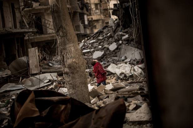 Syria, January 2017 - A little girl stands in the ruins and looks up into the sky for fighter jets in a destroyed street alley in East Aleppo. (Christian Werner/Zeitenspiegel) (Christian Werner/Zeitenspiegel)