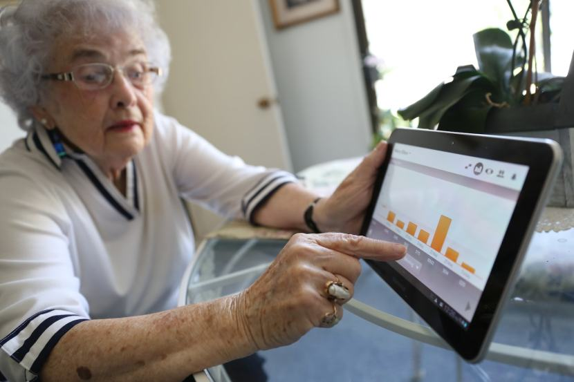 Woman holding a tablet showing her IoMT smart pill tracking application
