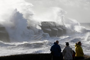 People watch the waves batter into the sea wall of a marina in Brighton, south England, Monday, Oct. 28, 2013. A major storm with hurricane force winds is lashing much of Britain, causing flooding and travel delays including the cancellation of roughly 130 flights at London's Heathrow Airport. Weather forecasters say it is one of the worst storms to hit Britain in years. (AP Photo/Sang Tan)