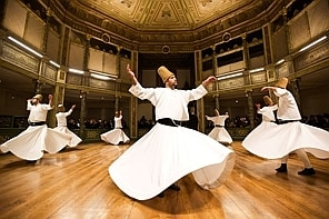 TOPSHOTS Whirling dervishes perform at the Galata Mevlevihane (The Lodge of the Dervishes) in Istanbul on December 18, 2013. The dervishes are adepts of Sufism, a mystical form of Islam that preaches tolerance and a search for understanding. Those who whirl, like planets around the sun, turn dance into a form of prayer. AFP PHOTO/GURCAN OZTURKGURCAN OZTURK/AFP/Getty Images