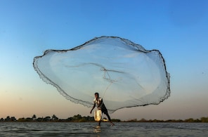 epa04085893 An Indian fisherman throws his net in a small pond at the outskirts of Mumbai, India, 18 February 2014.  EPA/DIVYAKANT SOLANKI