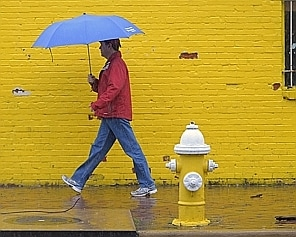 ALEXANDRIA VA APRIL 29: A pedestrian walks in heavy rain on the lower part of Prince Street in Alexandria VA , April 29, 2014. (Photo by John McDonnell/The Washington Post)
