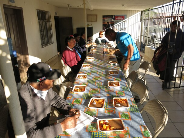 At a church-run shelter in Mexicali, migrants and deportees sit down for a 3 p.m. dinner of beans and potatoes.