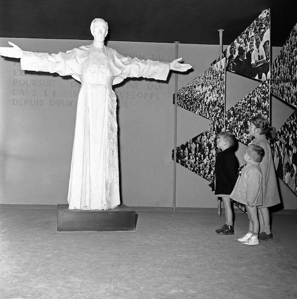 Children view a statue of Pope Pius XII at the Vatican pavilion at the world's fair in Brussels.