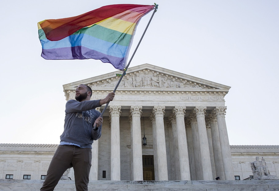 Vin Testa of Washington, DC, waves a gay rights flag in front of the Supreme Court before a hearing about gay marriage in Washington in an April 28, 2015 file photo. The U.S. Supreme Court ruled on June 26, 2015 that the U.S. Constitution provides same-sex couples the right to marry in a historic triumph for the American gay rights movement. The court ruled 5-4 that the Constitution's guarantees of due process and equal protection under the law mean that states cannot ban same-sex marriages. With the ruling, gay marriage will become legal in all 50 states.  REUTERS/Joshua Roberts/files