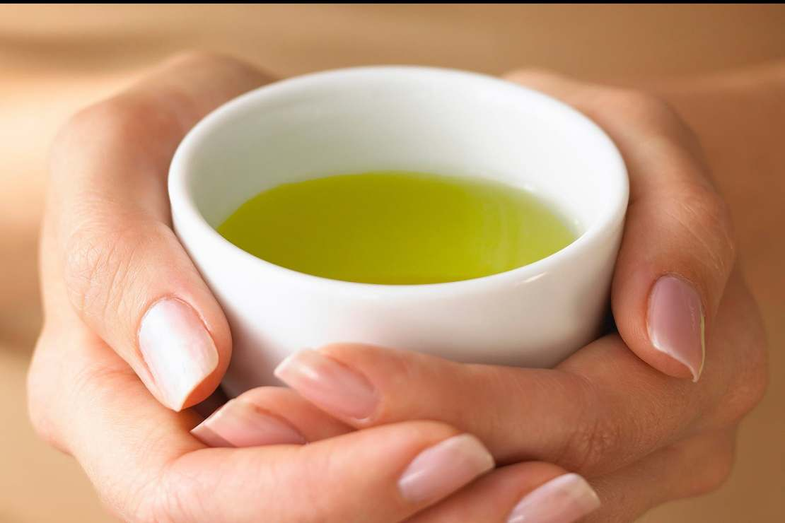 hands holding cup of green tea