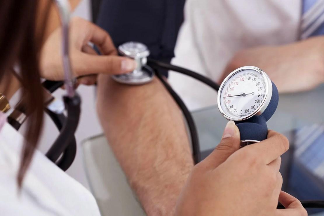 photo of nurse checking man's blood pressure