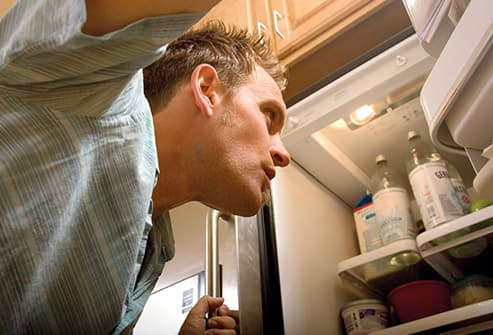 young man looking into refrigerator