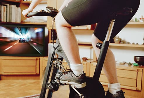 man riding stationary bike at home