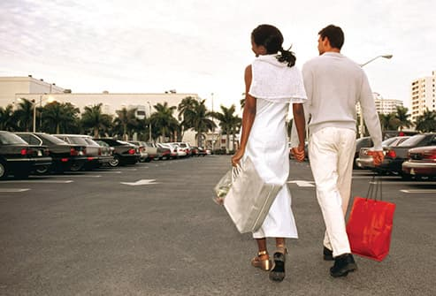 couple walking across mall parking lot