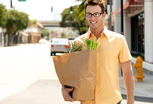 man carrying groceries home