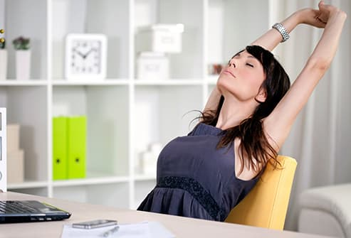 woman stretching at desk - 15 Ways to Sneak Exercise Into Your Day