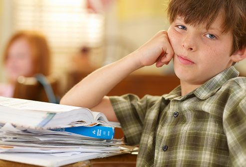 Bored boy sitting at desk in classroom