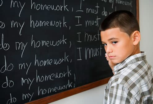 boy writing on blackboard as punishment