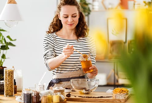 Woman pouring honey