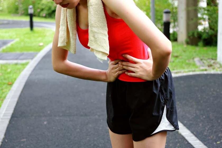woman with upset stomach on track